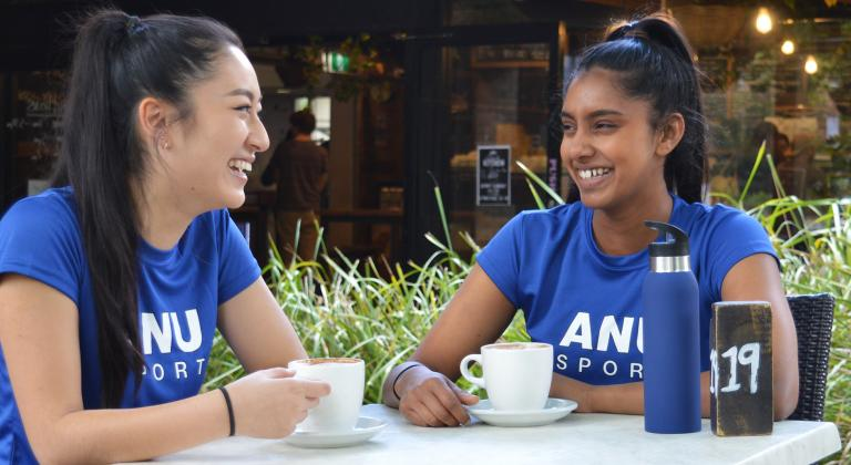 Two girls sitting having coffee in active wear