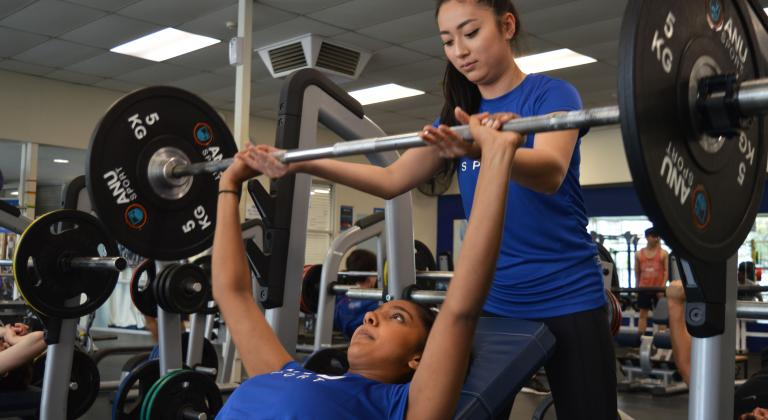 One girl spotting another girl whilst bench-pressing in blue shirts