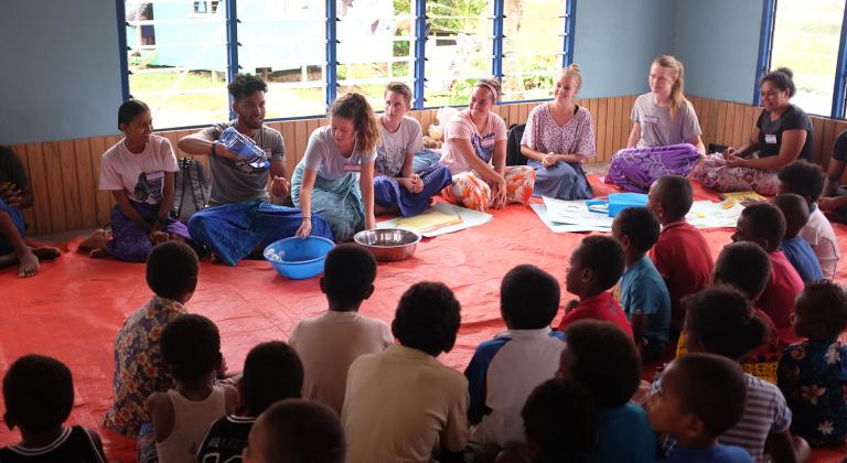 Group of students speaking with Fijian residents.