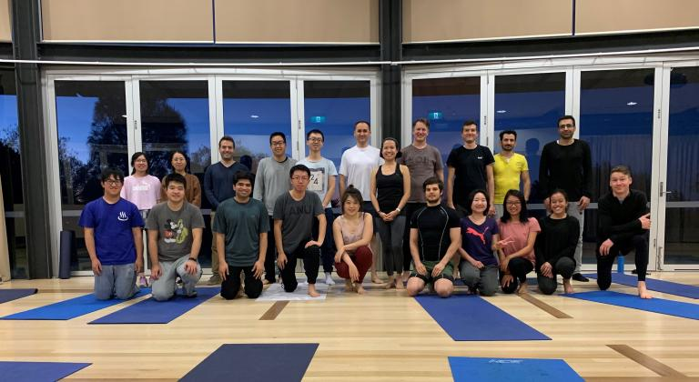 Group of people standing in front of yoga mats.